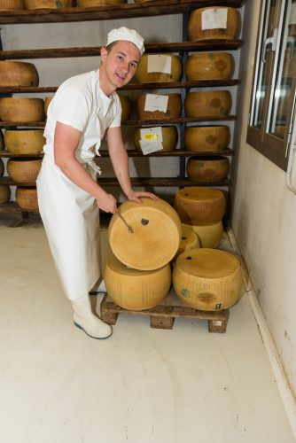 Luca hits cheese with a hammer to test its quality.