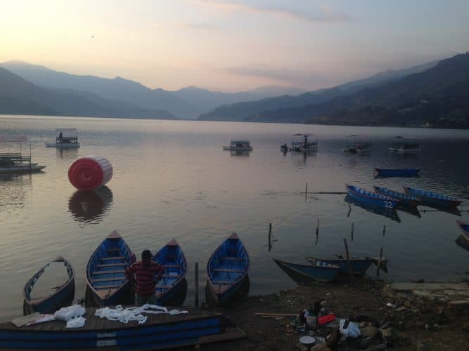 Paddle boats floating on Phewa Lake as the sun sets