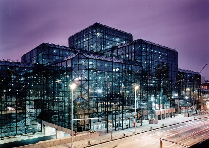 A Phenominal view of the Jacob J. Javits Convention Center as its clear glass strcture illuminates the sky at dusk.