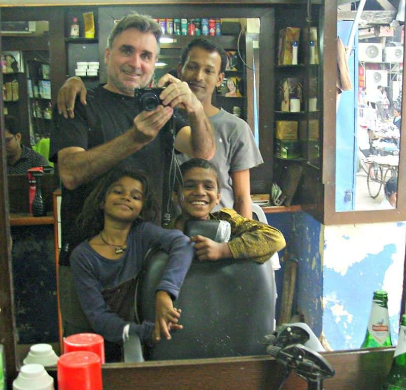 Bruce with local kids in New Delhi, India after a haircut and free massage.