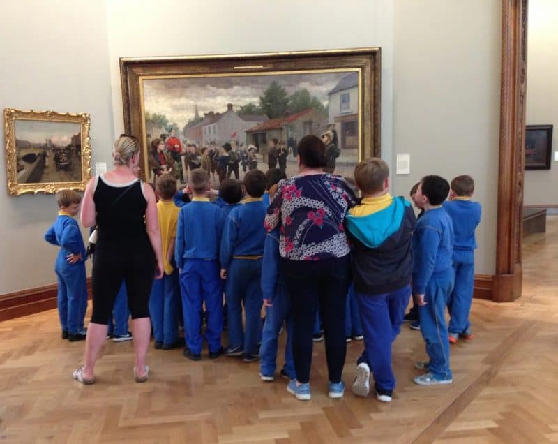 School children gather around an painting at the National Gallery in Dublin.