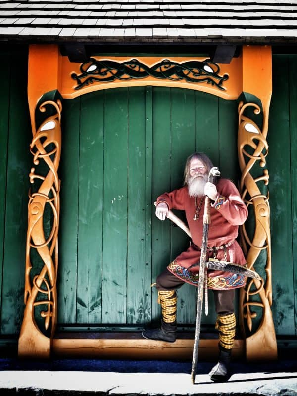 A traiditional viking leaning against a building in the village.