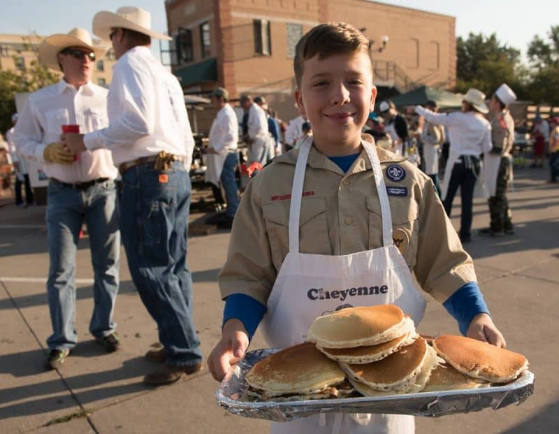A boy scout selling pancakes.