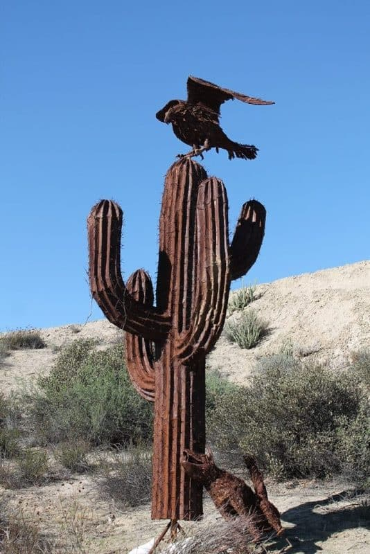 A steel cactus with a steel crow on top.