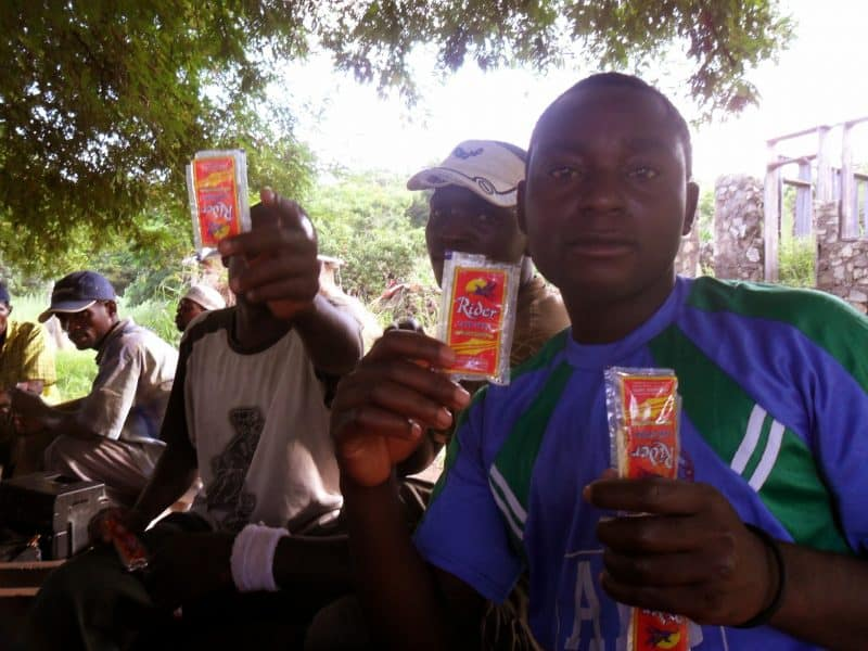 Young men idle away the afternoon under a tree drinking sachets of alcoholic spirits, listening to the radio and playing cards.