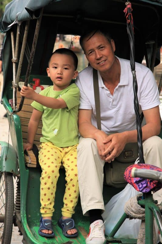 Father and son in a rickshaw in Suzhou.