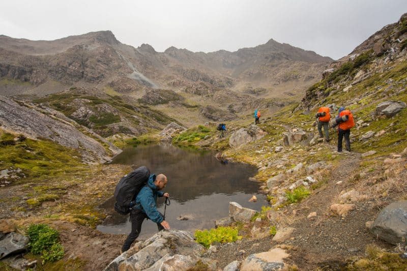 Hikers traveling alongside a pond in the Dientes in South America.