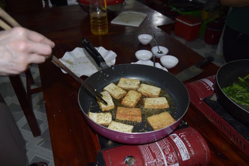 Cooking tofu during the cooking lesson.