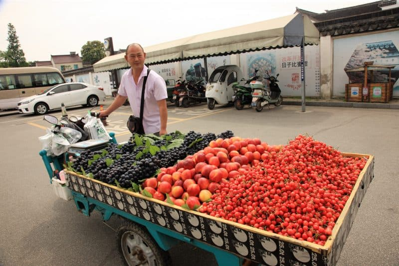 A friendly fruit vendor with his mobile stand in Suzhou.