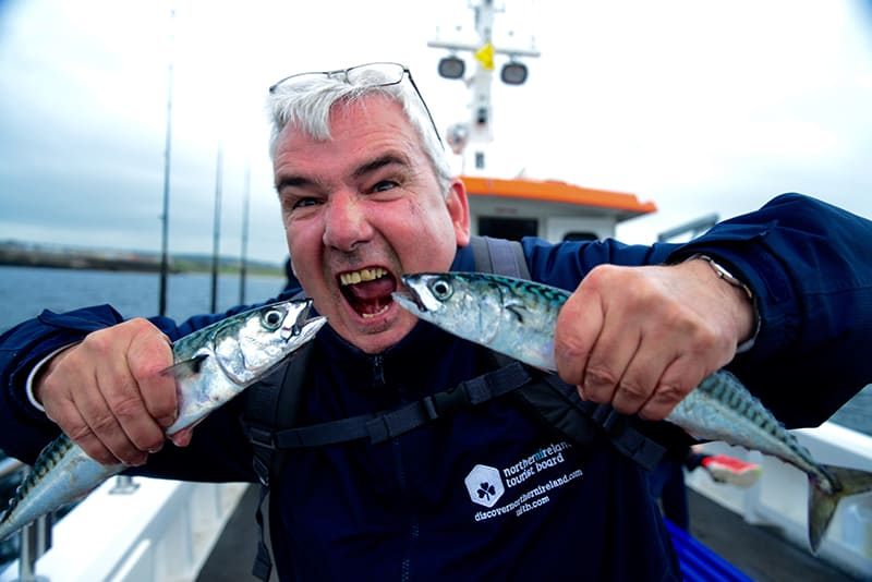 Northern Ireland Guide Billy Scott hams it up with two freshly-caught Mackerel on the Coastal Causeway. All photos by Sonja Stark.