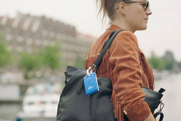 KLM Care Tag attached to a woman's purse, serving as a helpful city guide.