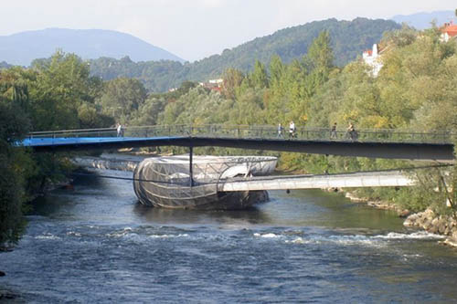 Right in the middle of the river Mur in Graz is a cafe and bar, accessible by bridges on either end.