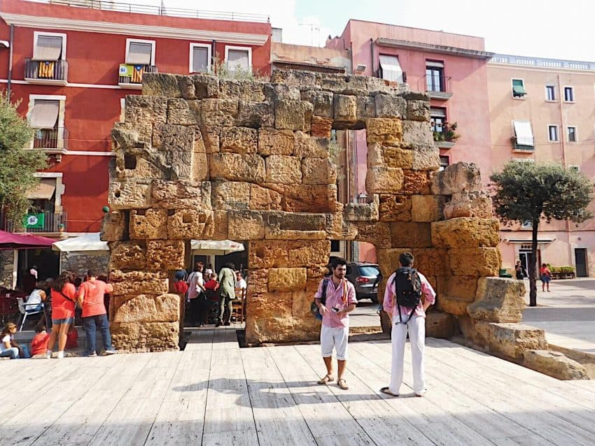 "Two Castellers stand infront of an Ancient Roman wall that remains in Tarragona's ""old town""."