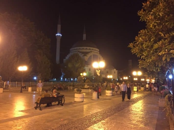 Pedestrians on Kolë Idromeno Street in Shkodër at night, with Ebu Bekr Mosque in the background