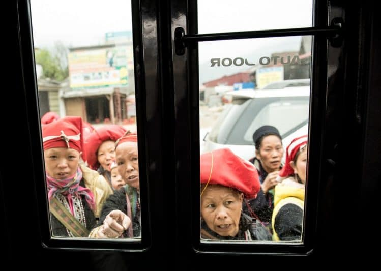 The Red Dao women wait eagerly at the bus door sizing up our group.