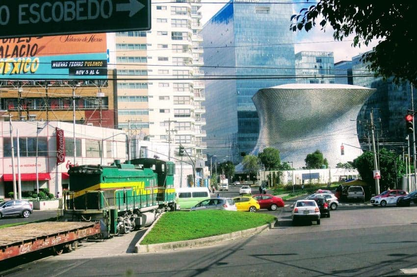 Incongruous sight - iconic Soumaya Museum, cars and diesel locomotive - Mexico City.