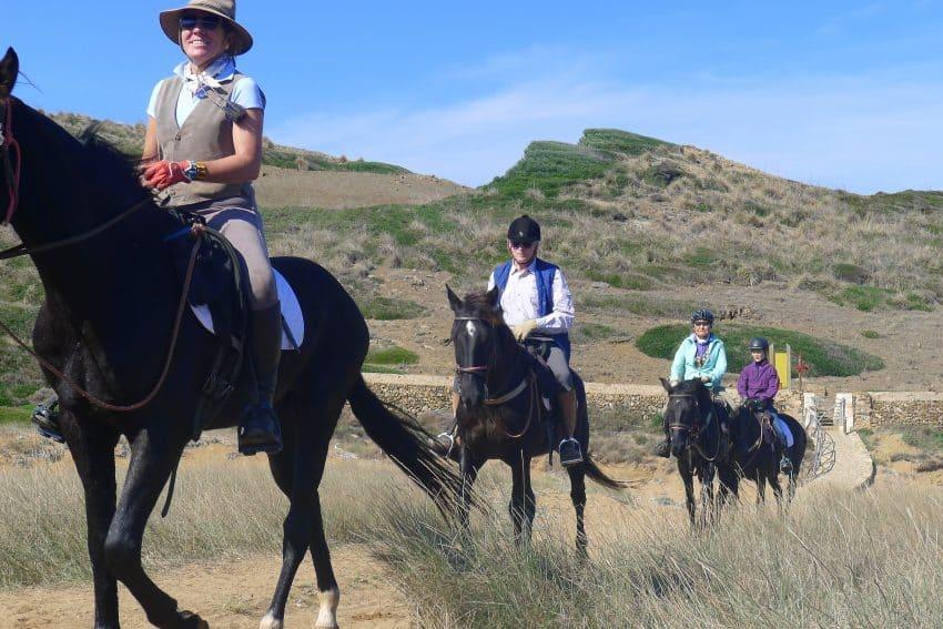 Riders on a horseback trek along Cami de Cavalls on Menorca in Spain.
