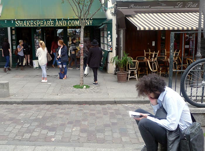 Reading the Bard in front of Shakespeare and Company bookstore, in Paris.