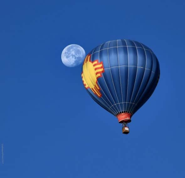 A balloon and the moon in wide open Albuquerque, NM.