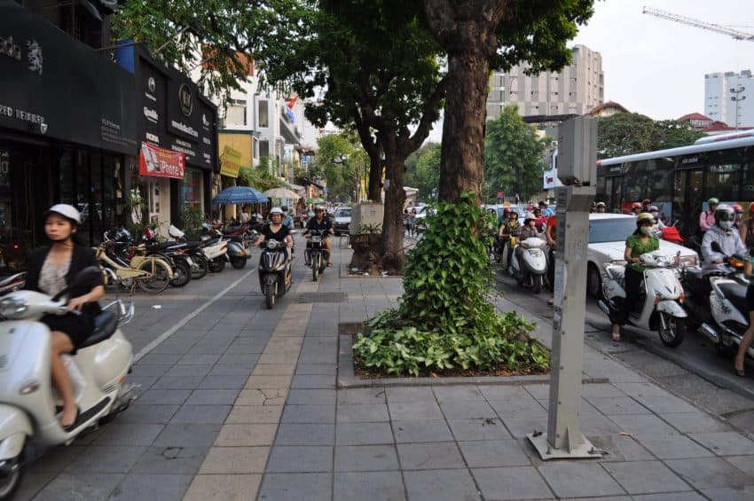 In Hanoi, the sidewalk is no place to hide from the onslaught of motorbikes.