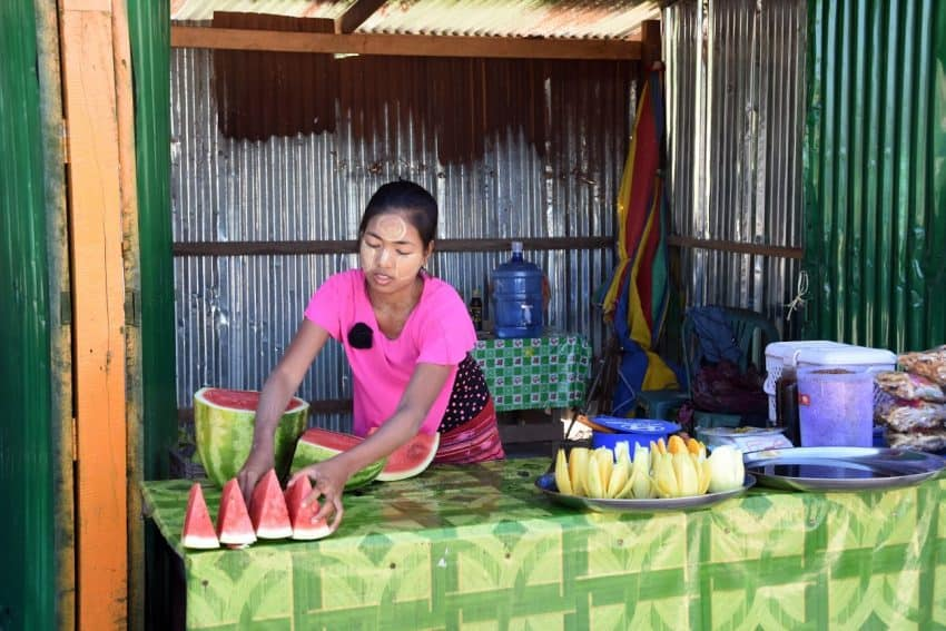 At a watermelon stall, a local girl covered her face with thanaka.