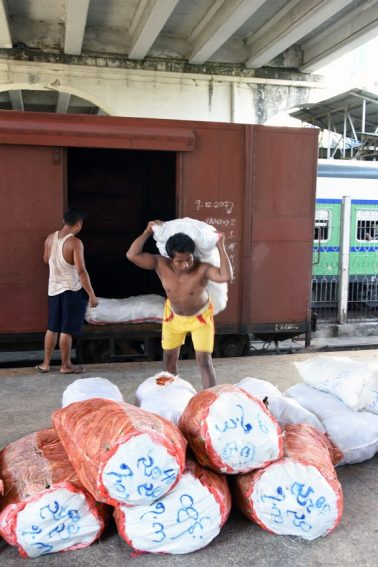 Workers unload cargo at Yangon Station.