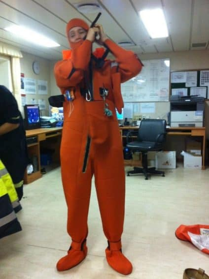 Preparation onboard: Donning a safety suit.