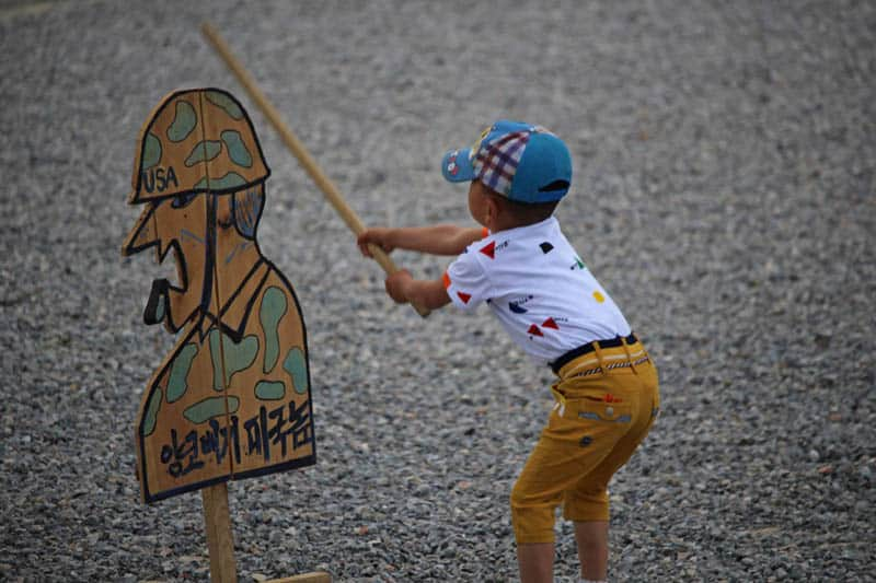 Children hitting these wooden cutouts of U.S. Army soldiers with sticks.