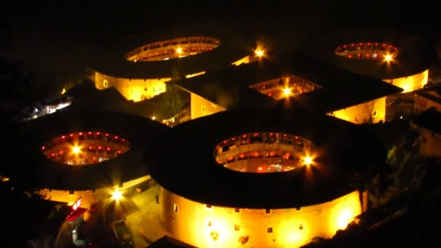 The Tianluokeng tulou cluster lit up at night during Chinese New Year.
