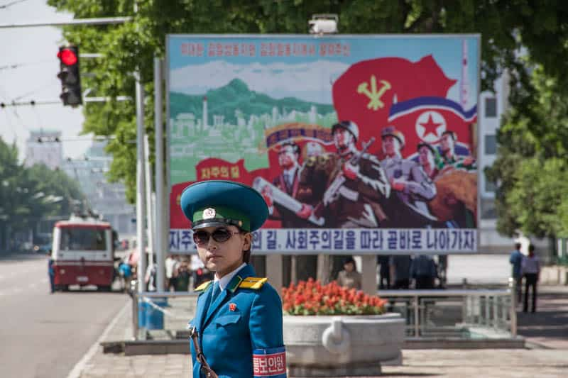 A uniformed woman directs traffic in Pyongyang. Behind her is one of the countless propaganda posters that are ubiquitous in the city.