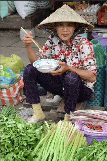 A lady having lunch in the market.
