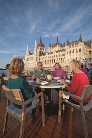 Adults dine on the deck of the Viking Longship in Budapest. Photo courtesy of Viking Cruises. | GoNOMAD Travel