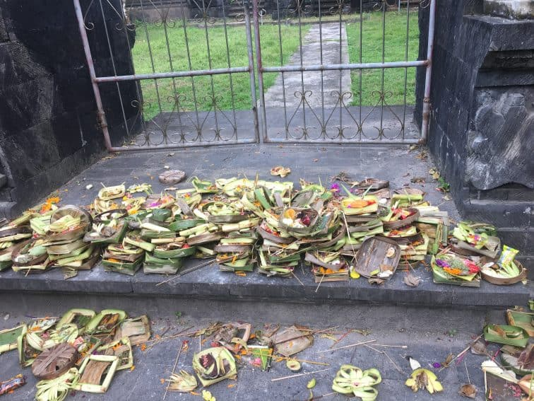Offerings strewn along a sidewalk during the Nyepi celebration in Bali. | GoNOMAD Travel