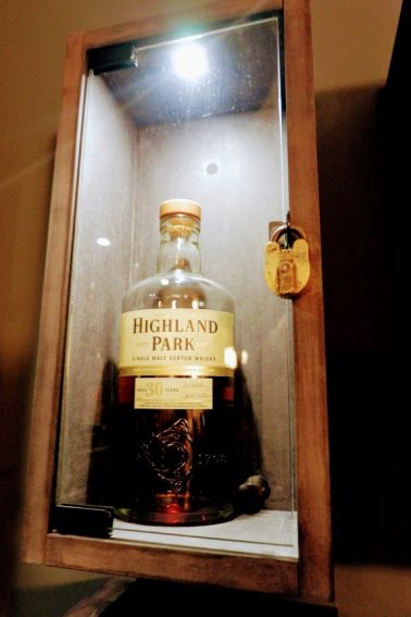 "inside Golden Promise's ""The Keep"" with a purchased bottle of Whiskey in a glass case with custom iron lock."