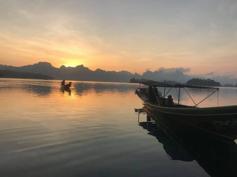 The sun rises over the mountains near Chiaw Laan Lake, Thailand. | GoNOMAD Travel