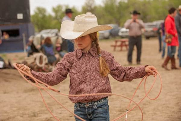 Harley Meged practices roping back behind the bucking chutes while her family is involved in helping to run the Bucking Horse Sale.