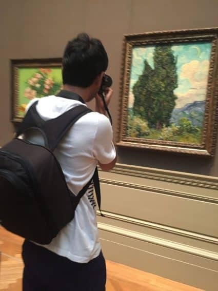 A man takes a photo of a van Gogh in the Metropolitan Museum of Art, New York City