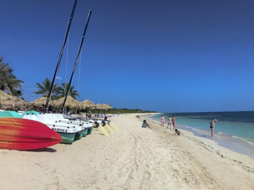 Cubans and tourists visit the beautiful Playa Ancon. | GoNOMAD Travel