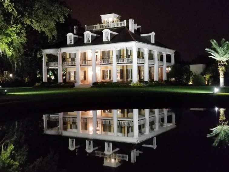 Houmas House by night, as reflected in the pond near the oak-lined entrance to this historic plantation house. | GoNOMAD Travel