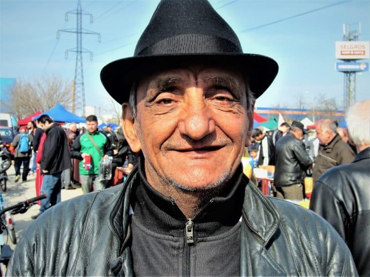 Weather-beaten Roma vendor posing for us at the flea market in Bucharest