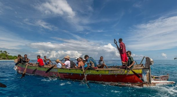 Rowing a large boat off the coast of Papua New Guinea.