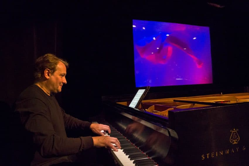 The pianist Christopher O'Riley plays as the puppet show ensues behind him.