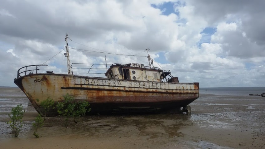 A fishing boat at low tide along the beach.