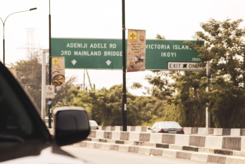 Stopping to take a picture of two signs at Ikoyi under bridge, as defines the two different islands Mainland and Eti Osa