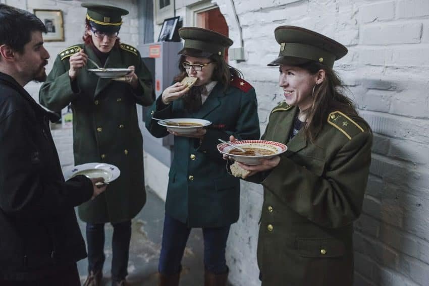 Visitors wearing the jackets and hats from the Cold War have a simple lunch of soup and bread at 10-Z. (photo courtesy of 10-Z Museum)