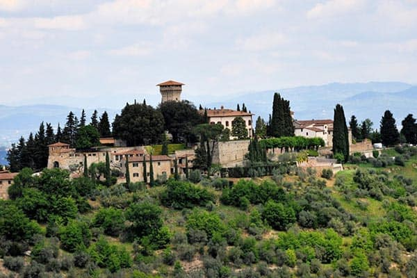 View to Castello Vicchiomaggio from Castello Verrazzono above the vineyards, Greve, Tuscany, Italy. GoNOMAD Travel