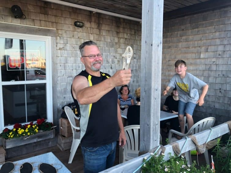 "Eric Wagner holds up a ""PEI Hammer"" at his daughter Courtney's waterfront restaurant, The Catch, in West Point, PEI."