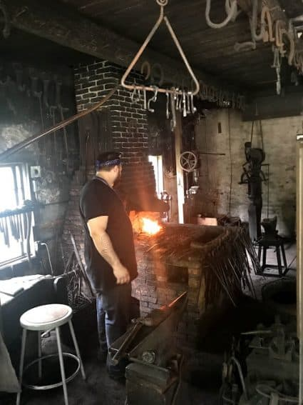 A blacksmith working inside the shop at Shelburne Museum.