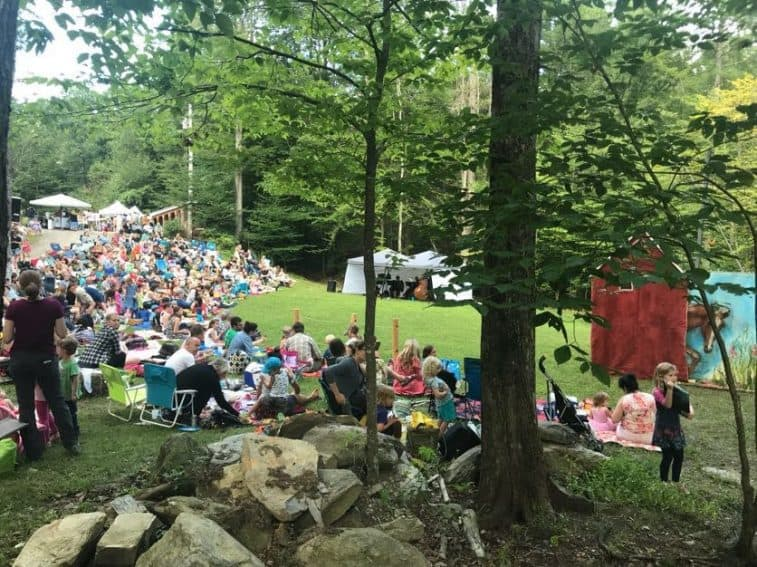 Visitors to Moonrise Farms sitting on picnic blankets and lawn chairs to view the performance.