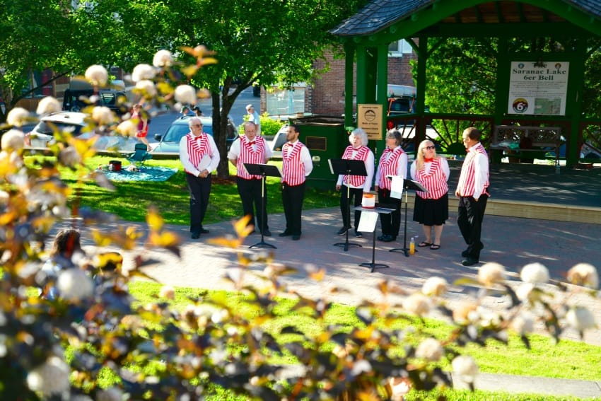 The Adirondack Barbershop Coalition sang familiar show tunes at Berkeley Green, a park across the street from the Hotel Saranac.